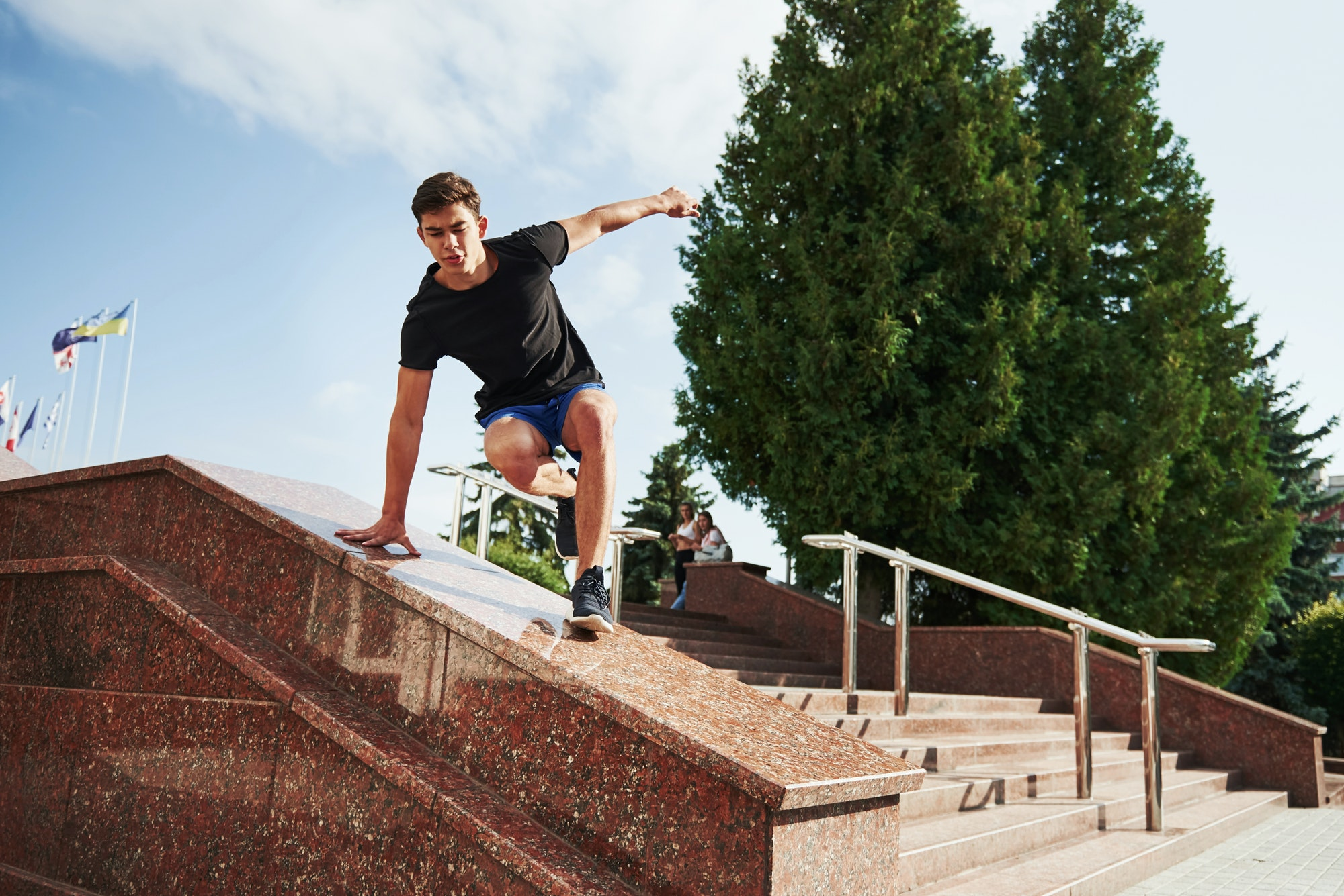 Above the obstacle. Young sports man doing parkour in the city at sunny daytime