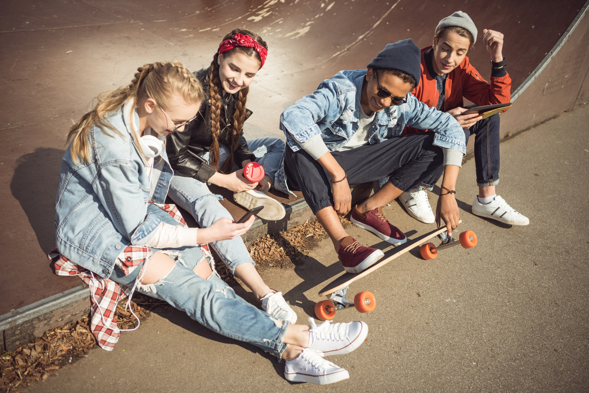 Teenagers group sitting sitting together and using digital devices at skateboard park